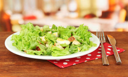 Caesar salad on white plate, on bright background photo