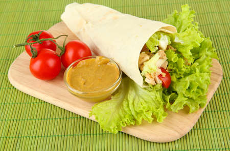 Kebab - grilled meat and vegetables, on wooden board, on bamboo mat background photo