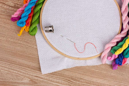 The embroidery hoop with canvas and bright sewing threads for embroidery in the table photo