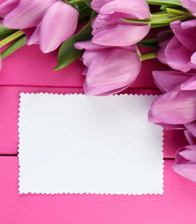 Beautiful bouquet of purple tulips and blank card on pink wooden background photo