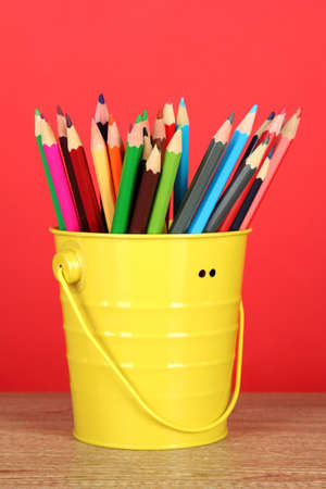 hued: Colorful pencils in pail on table on red background Stock Photo