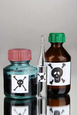 meanness: Deadly poison in bottles on grey background