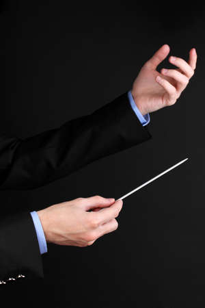 Music conductor hands with baton isolated on black photo