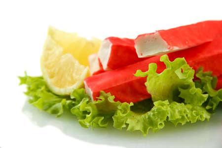 crabmeat: Crab sticks on lettuce leaves with lemon, isolated on white Stock Photo