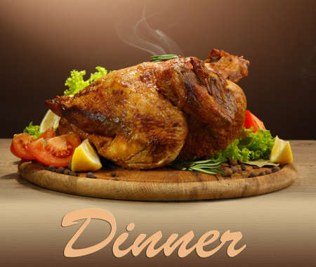 sample tray: Whole roasted chicken with vegetables, on wooden table, on brown background