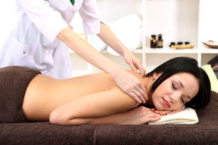 masseur: Beautiful young woman in spa salon getting massage, on bright background