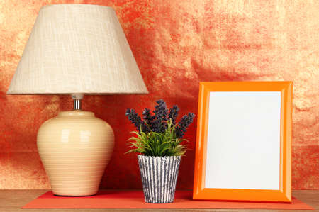 Colorful photo frame, lamp and flowers on wooden table on red background photo