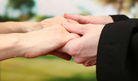 reverent: Priest holding woman hands, on green background