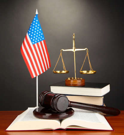 proceeding: Wooden gavel, golden scales of justice  and books on grey background Stock Photo
