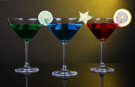 Alcoholic cocktails in martini glasses on dark yellow background photo