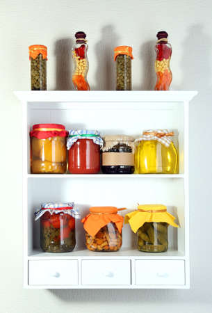 Homemade preserves on beautiful white shelves photo