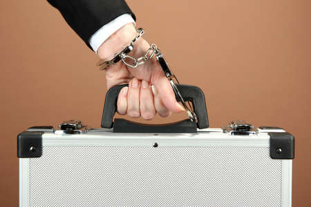 Hand with handcuff and suitcase, on color background photo