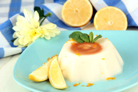 Lemon Panna Cotta with orange zest and caramel sauce, on color wooden background photo