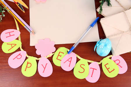 odd jobs: Writing letter of congratulations to Easter holidays on wooden table close-up