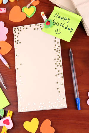 odd jobs: Writing letter of congratulations to Happy Birthday on wooden table close-up