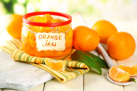 Orange jam with zest and tangerines, on white wooden table photo