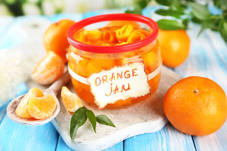 Orange jam with zest and tangerines, on blue wooden table photo