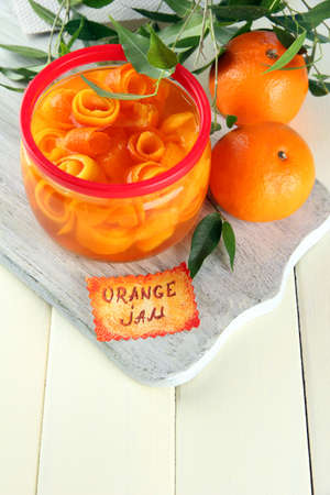 zest: Orange jam with zest and tangerines, on white wooden table
