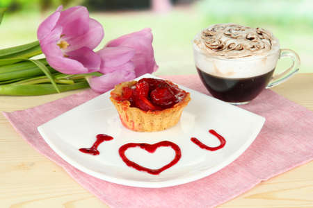 Sweet cake with strawberry and sauce on plate, with coffee, on bright background photo