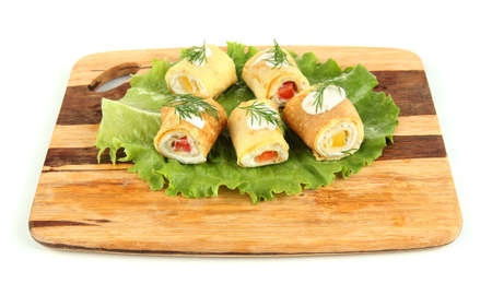 Egg rolls with cheese cream and paprika, on wooden board, isolated on white photo