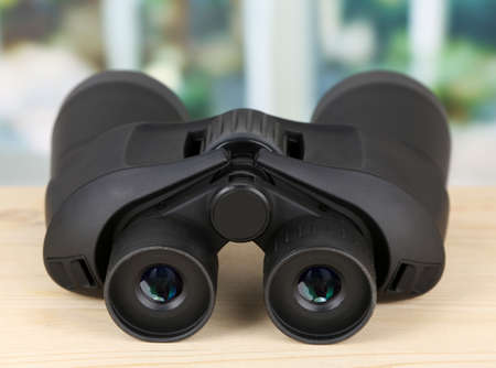 Black modern binoculars on wooden table on window background photo