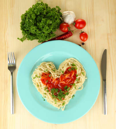 Cooked spaghetti carefully arranged in  heart shape and topped with tomato sauce, on  wooden background photo