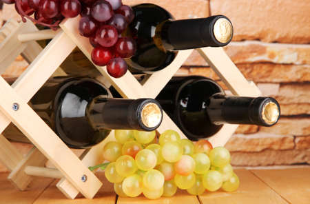 Bottles of wine placed on wooden stand on stone wall background photo