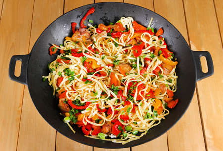 wok: Noodles with vegetables on wok on wooden background Stock Photo