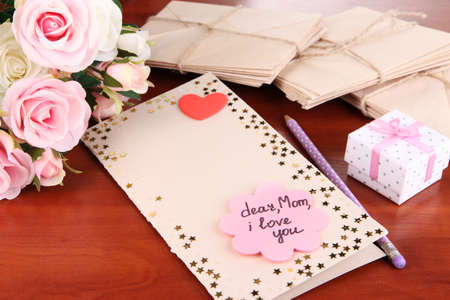 Writing letter of congratulations to mother's Day on wooden table close-up Stock Photo - 19607385