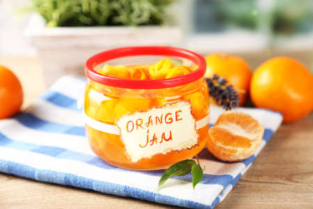 Orange jam with zest and tangerines, on wooden table photo