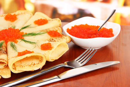 Delicious pancakes with red caviar on table in cafe photo