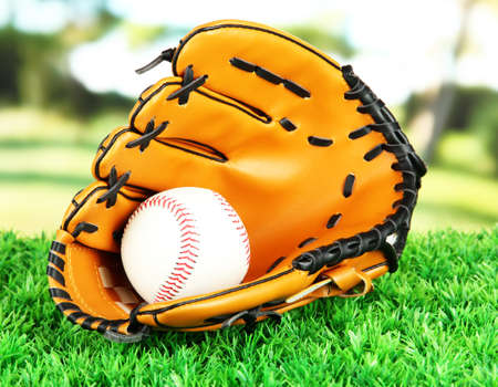Baseball glove and ball on grass in park photo