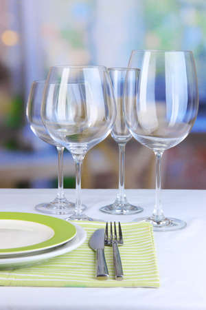 Table setting with glasses for different drinks on table on room background photo