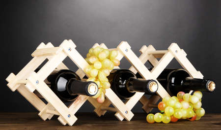 cabarnet: Bottles of wine placed on wooden stand on grey background