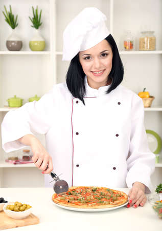 Beautiful girl chief-cooker with pizza on kitchen background photo