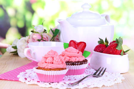 Beautiful strawberry cupcakes and flavored tea on dining table on natural background photo