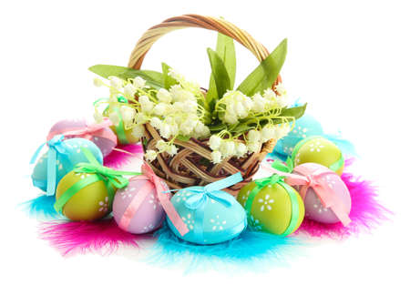 Beautiful easter eggs and lilies of the valley in basket , isolated on white photo