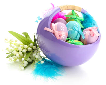 Beautiful easter eggs in basket and lilies of the valley, isolated on white photo