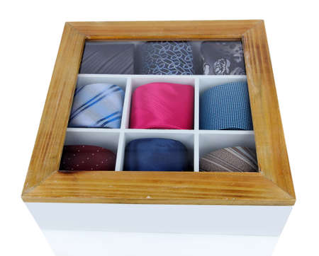 Neckties in wooden box isolated on white photo