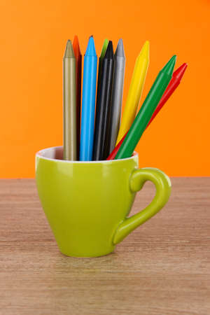 Colorful pencils in cup on table on orange background photo