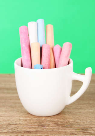 hued: Colorful chalks in cup on table on green background