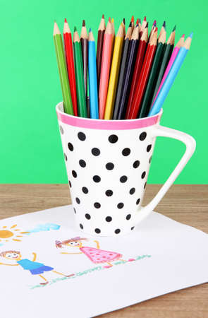 Colorful pencils in cup on table on green background photo