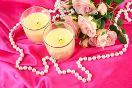 Candle on pink fabric close -up photo