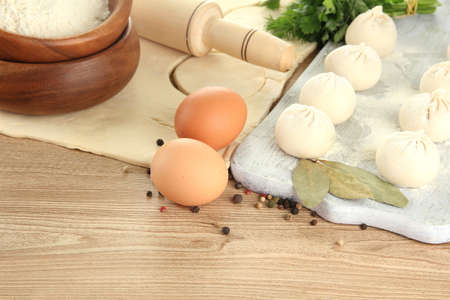 Raw dumplings, ingredients and dough, on wooden table photo