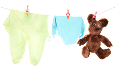 Baby clothes hanging on clothesline, isolated on white photo