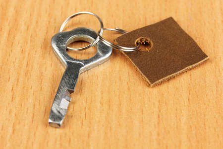 Key with leather trinket on wooden background photo
