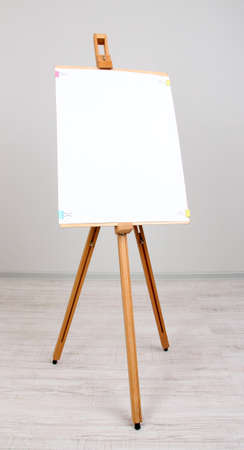 Wooden easel with clean paper in room photo