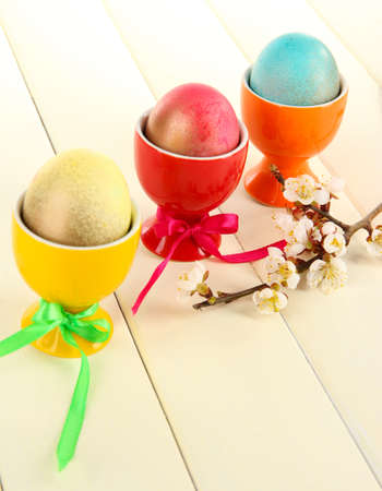 Easter eggs in colorful trays on wooden table photo