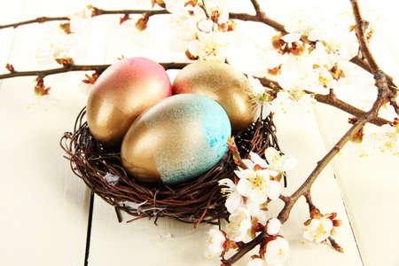 Easter eggs in nest with flowering branches on wooden table photo