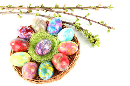 Beautiful Easter eggs in wicker basket isolated on white photo
